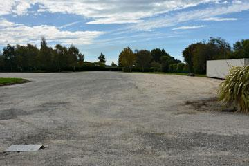 Large gravel parking area behind the main building