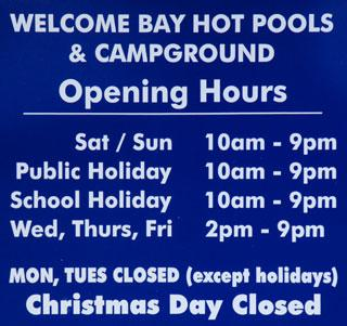 Welcome Bay Hot Water Pools and Campground opening hours sign
