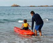 Father helping son launch canoe